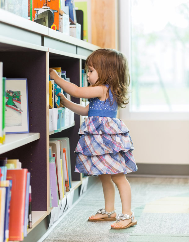 Young girl choosing books from shelf